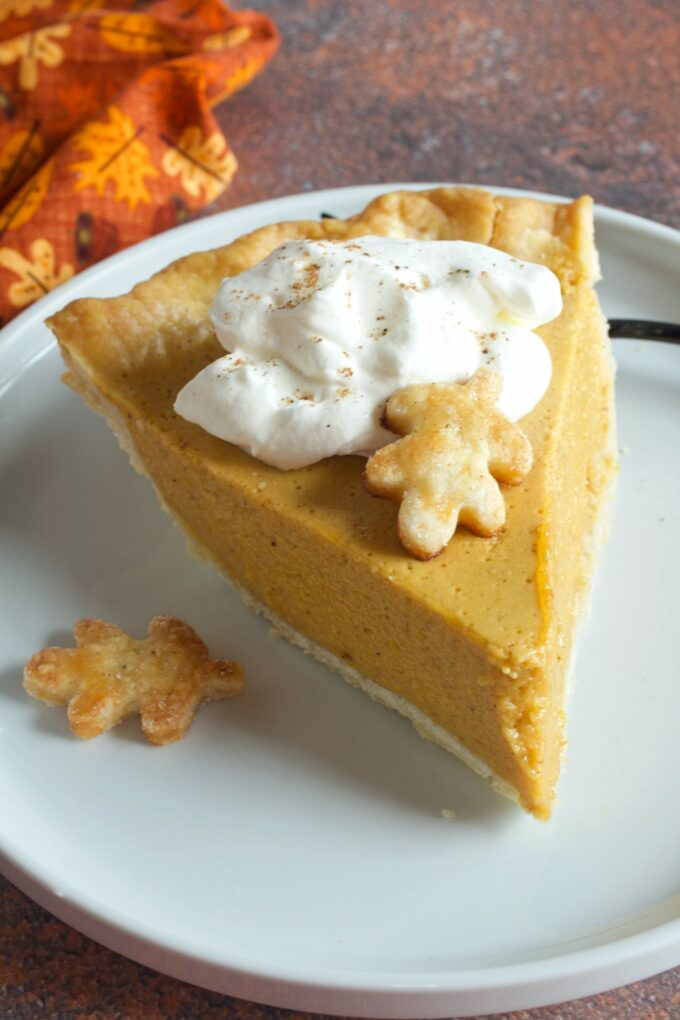 A slice of light and creamy Pumpkin Chiffon Pie with a pastry leaf and a dollop of whipped cream.